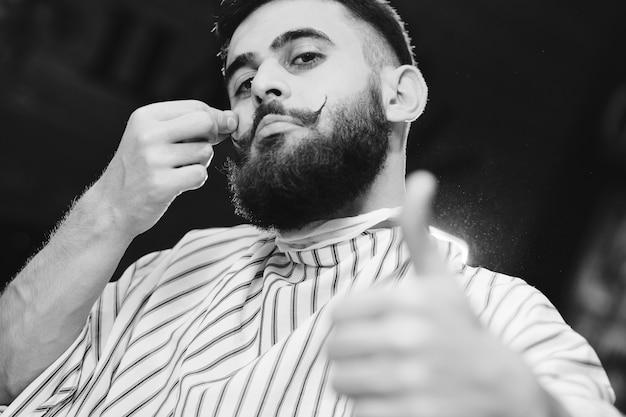 Симпатичный молодой человек с красивыми усами и бородой, сидя в кресле в парикмахерской Premium Фотографии
