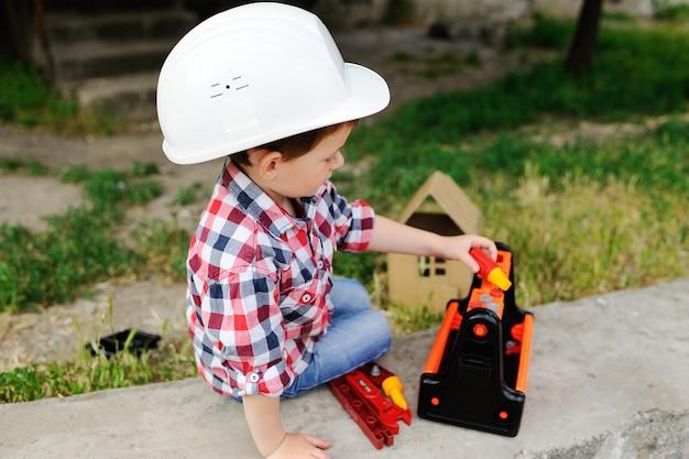 Мальчик в белом строительном шлеме Premium Фотографии