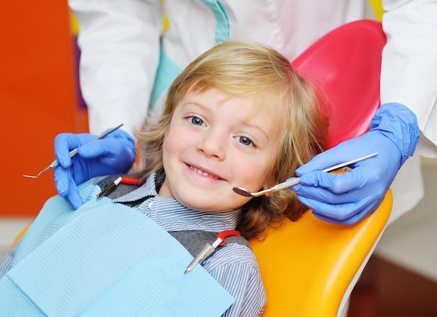 Улыбающийся ребенок со светлыми вьющимися волосами на экзамене в стоматологическом кресле Premium Фотографии