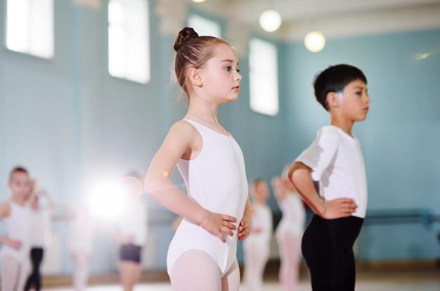 バレエスタジオの若いダンサー。若いダンサーは、教室でのウォームアップ中に体操を行います。スポーツ、体操、子どもの発達 Premium写真