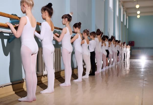 バレエスタジオの若いダンサー。若いダンサーは教室でウォームアップしながらバレエやバレで体操をします。 Premium写真