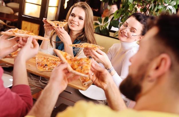 友達のグループが話し、カフェで笑ってピザを食べます。 Premium写真