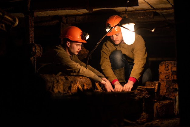 Двое молодых парней в рабочей форме и защитных шлемах сидят в низком туннеле. шахтеры Premium Фотографии