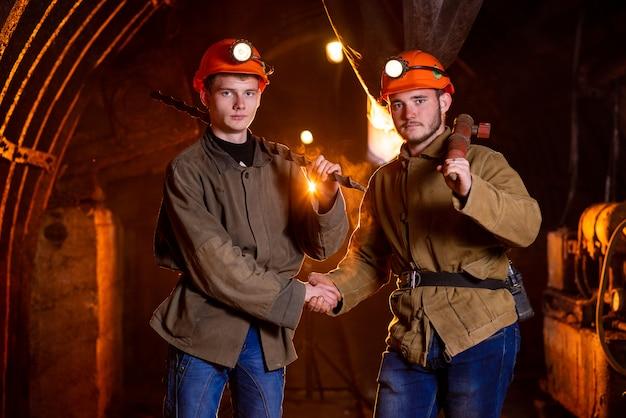 Два молодых парня в рабочей форме и защитных шлемах, пожимающие друг другу руки. рабочие шахты. шахтеры Premium Фотографии