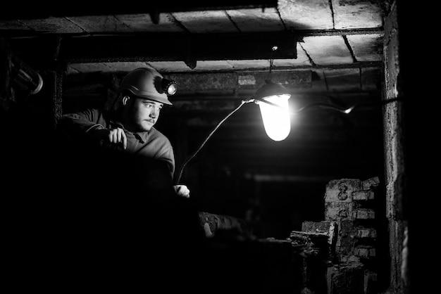 保護スーツとヘルメットの男は燃えているスクラップブックとトンネルに座っています Premium写真