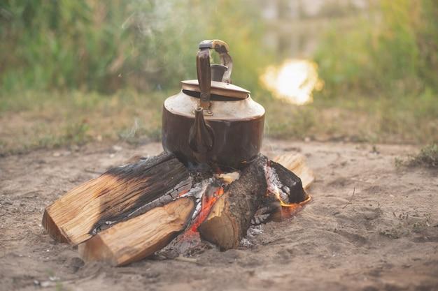 古い鉄のやかんは燃える木、キャンプの上に立つ Premium写真