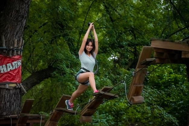 Веревочный парк, полоса препятствий, активный образ жизни, красивая девушка занимается спортом Premium Фотографии