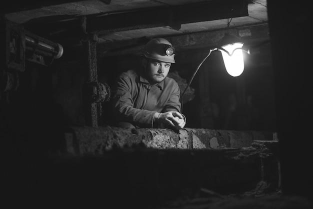 保護スーツとヘルメットを着た若い男が燃えるスクラップブックのトンネルに座っている Premium写真