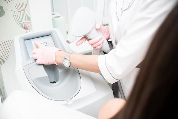 ピンクの手袋をした医師の手が脱毛のためにデバイスを保持し、タッチスクリーンを押します。制御装置の概念、レーザー脱毛 Premium写真