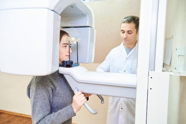 Стоматологическая томография. девочка-пациентка стоит в томографе, врач возле пульта управления Premium Фотографии