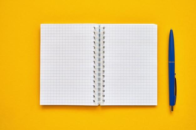 空白の四角いページと青ペンで開いているノートブックの平面図。黄色の背景、スパイラルメモ帳に学校のノート。学校概念に戻る Premium写真
