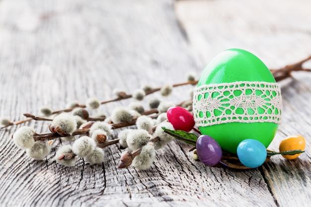 木製の背景にレースと柳の枝で飾られた緑のイースターエッグ。セレクティブフォーカス、コピースペース Premium写真