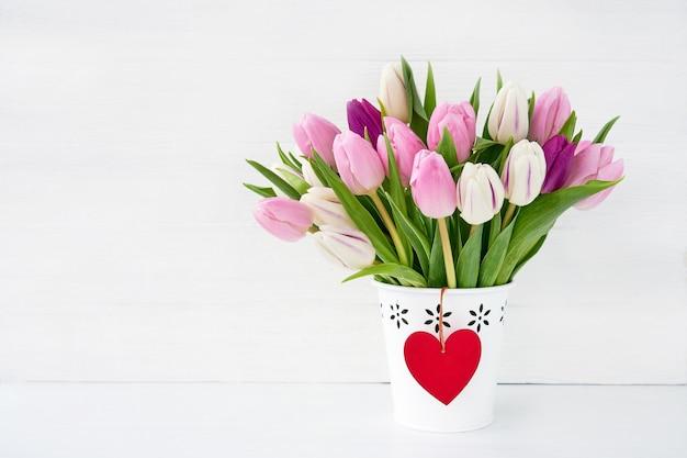 赤いハートの白い花瓶にピンクと白のチューリップの花束。バレンタインデーのコンセプトです。コピースペース Premium写真