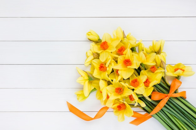 白い木製のテーブルの上のリボンで飾られた新鮮な春の水仙の花束。 Premium写真