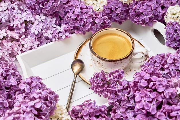 Сирень цветет предпосылка с чашкой кофе в середине с космосом экземпляра. Premium Фотографии