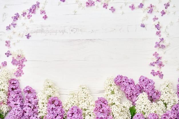 白い木製の背景にカラフルなライラック色の花の境界線。 Premium写真