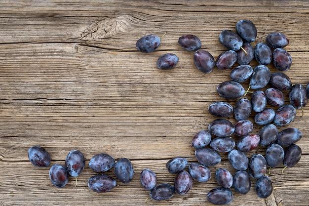 Свежие синие сливы на старый деревянный стол Premium Фотографии
