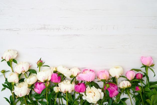 白い木製のテーブルに白とピンクの牡丹。 Premium写真