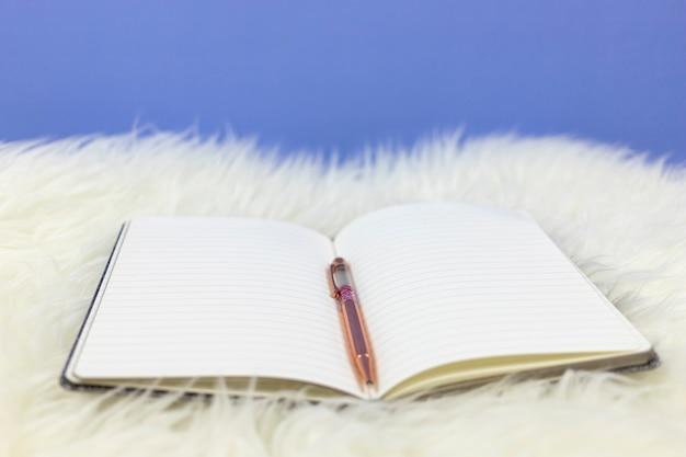 白い毛皮の背景にピンクのペンで空のノートを開きます。 Premium写真