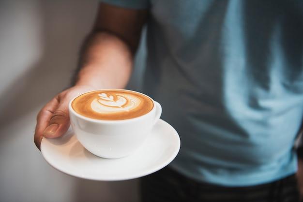 カフェで泡状の泡、コーヒーカップ上面とラテやカプチーノを持っている手。 Premium写真