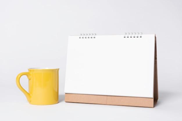 白紙スパイラルカレンダーとモックアップテンプレート広告とブランドの背景の黄色のカップ。 Premium写真