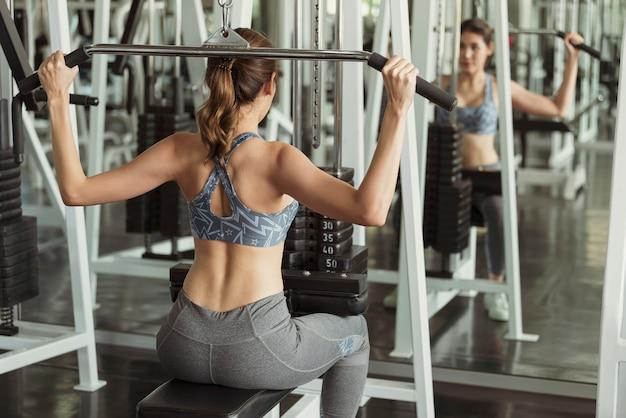 若いアジア女性がジムでバーベルを持ち上げます。健康的なライフスタイルとトレーニングの動機の概念。 Premium写真