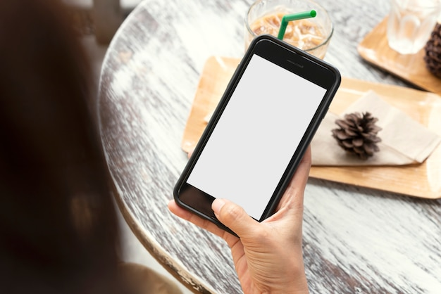 カフェの木製テーブルに空白の画面を持つ携帯電話を使用して保持している手のモックアップ画像。 Premium写真