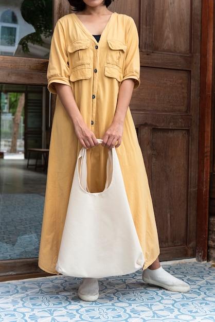 Девушка держит сумку холст ткани Premium Фотографии