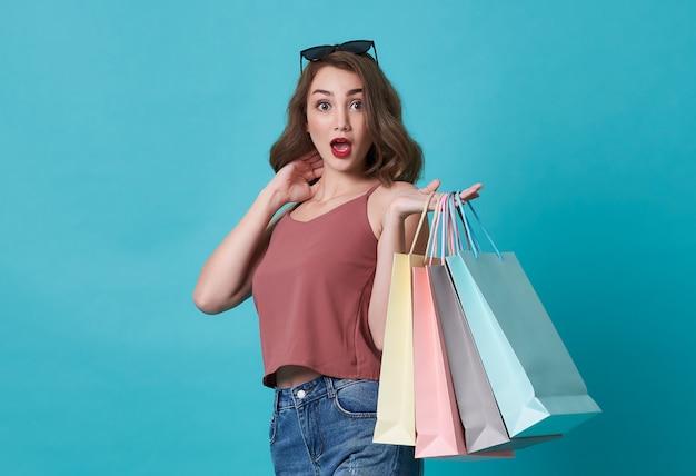 Взволнованная молодая женщина, держащая сумки Premium Фотографии