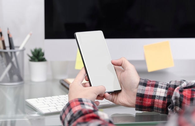 オフィスのテーブルに空白の画面を持つ携帯電話を持っている手のモックアップ画像。彼女のスマートフォンのコンセプトにソーシャルネットワーク。 Premium写真
