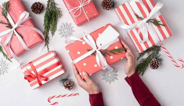 クリスマスの日に人々に与える赤いギフトボックスを持っている手。休日のお祝いと新年あけましておめでとうございますコンセプト。 Premium写真