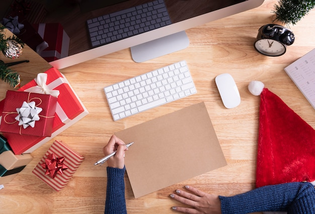 手書きのデスクトップ上のメリークリスマスと幸せなクリスマスの装飾のためのグリーティングカードのモックアップ。 Premium写真