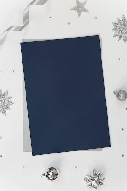 クリスマスの装飾と紙吹雪と白のグリーティング紙カードをモックアップします。 Premium写真