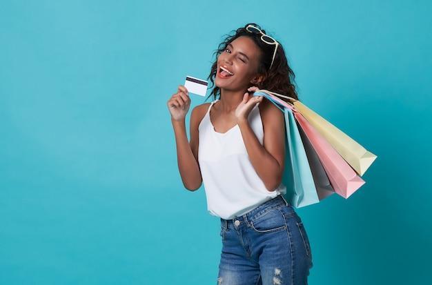 Портрет счастливой молодой женщины показывая кредитную карточку и хозяйственную сумку изолированную над голубой предпосылкой. Premium Фотографии