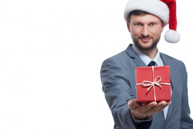 クリスマスボーナス。少し赤いクリスマスプレゼントに選択的に焦点若い実業家が抱いている。 Premium写真