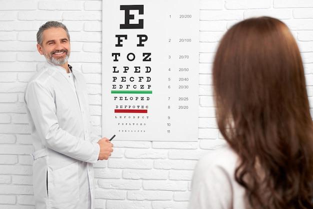 テスト視力検査表の近くに白い制服立っている医者。 Premium写真