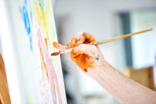 男性アーティストの手のクローズアップ、ブラシを押しながら画家のスタジオで豊かなオレンジ色の塗料を塗る。 Premium写真