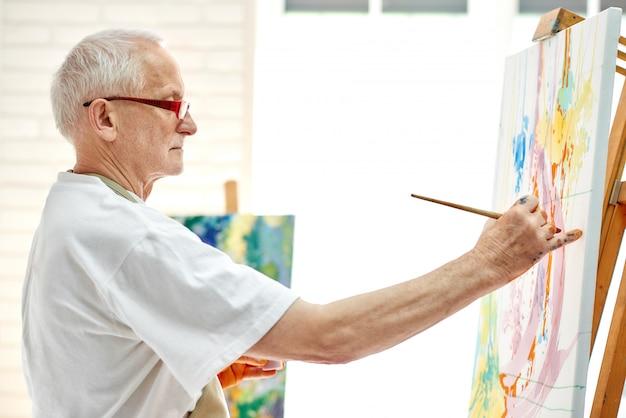 明るいスタジオでカラフルな絵を描く創造的な上級画家。 Premium写真