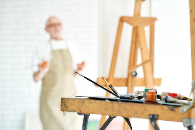 描画機器やツール、アーティストの水彩ブラシ、男性アーティストとイーゼルのクローズアップ Premium写真