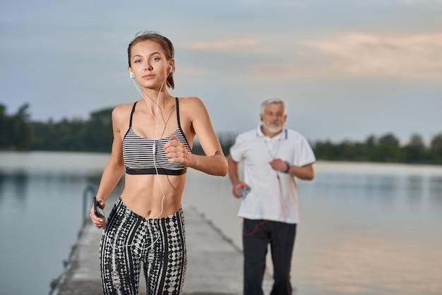 夕方には湖の近くを走るフィット姿でスポーティな女の子。年配の男性が後ろに走っています。 Premium写真