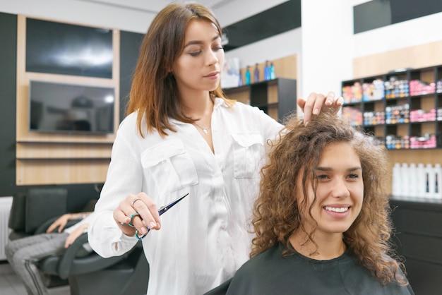 巻き毛の女性クライアントを笑顔のための新しいヘアドレスをしています。 Premium写真