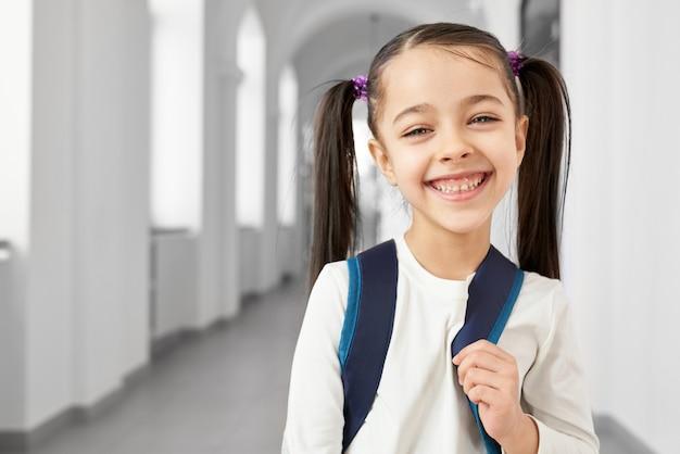 小学校の笑顔の長くて明るい廊下に立っている髪の尾を持つかわいい、かわいい、幸せな女子高生 Premium写真