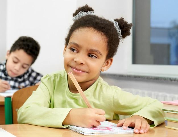 生徒は窓の近くの机に座って、ペンを保持しています。 Premium写真