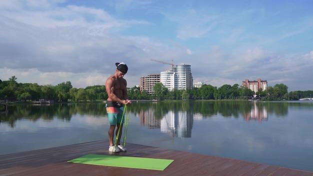 Мускулистый мужчина держит расширитель и тянет его к себе Premium Фотографии