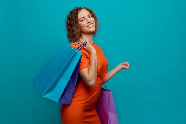 ショッピングの後カメラを見てオレンジ色のドレスの女の子 Premium写真