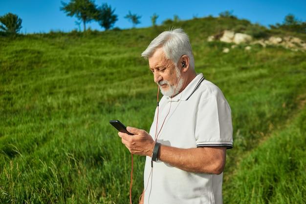 彼の携帯電話を屋外で見ている老人の横顔。 Premium写真