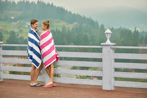 テラスで立っているカップル、お互いの目で見ています。 Premium写真