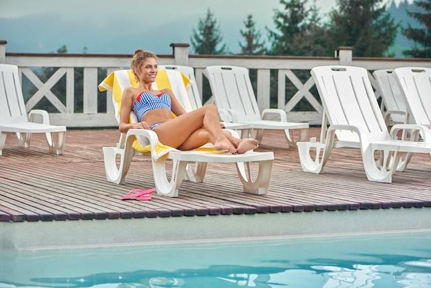 プールの近くのタオルで白いラウンジャーで横になっているセクシーな女の子。 Premium写真