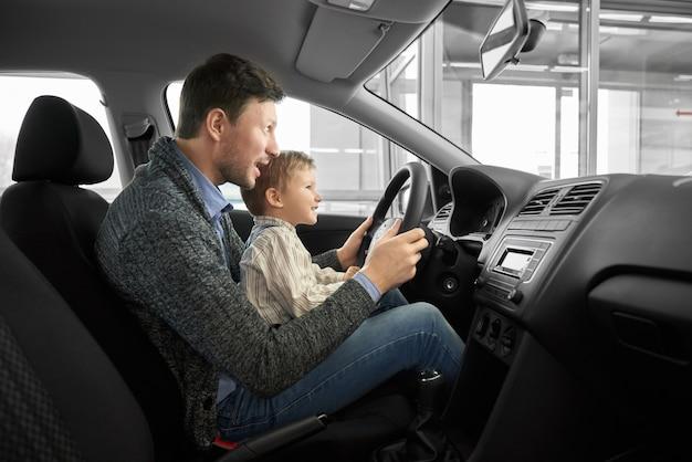 面白いパパと息子の新しい自動車のドライバーの座席に座って Premium写真