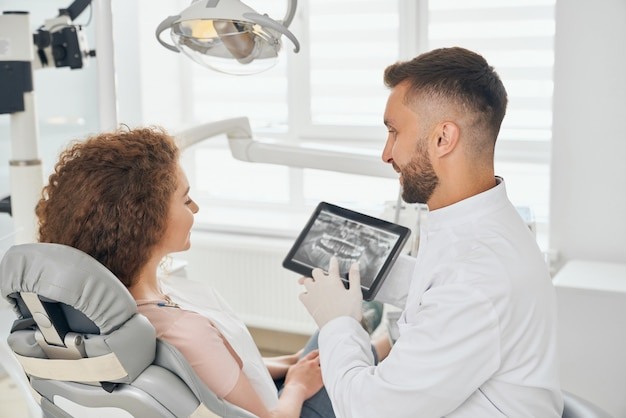 現代の歯科医院で働く男性歯科医 Premium写真